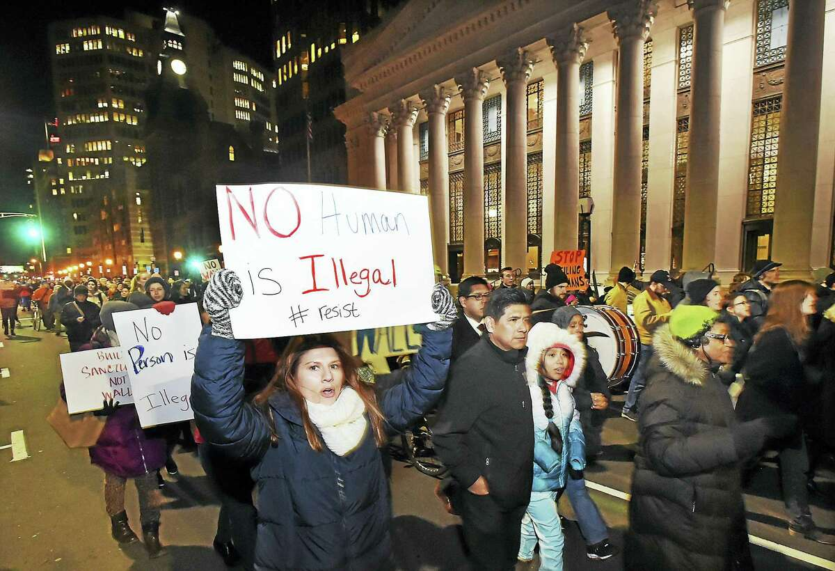 Protesters march up Church Street Thursday demonstrating against President Donald J. Trump's policies on enforcing U.S. immigration law and againt sanctuary cities, after a rally at the entrance to New Haven City Hall.