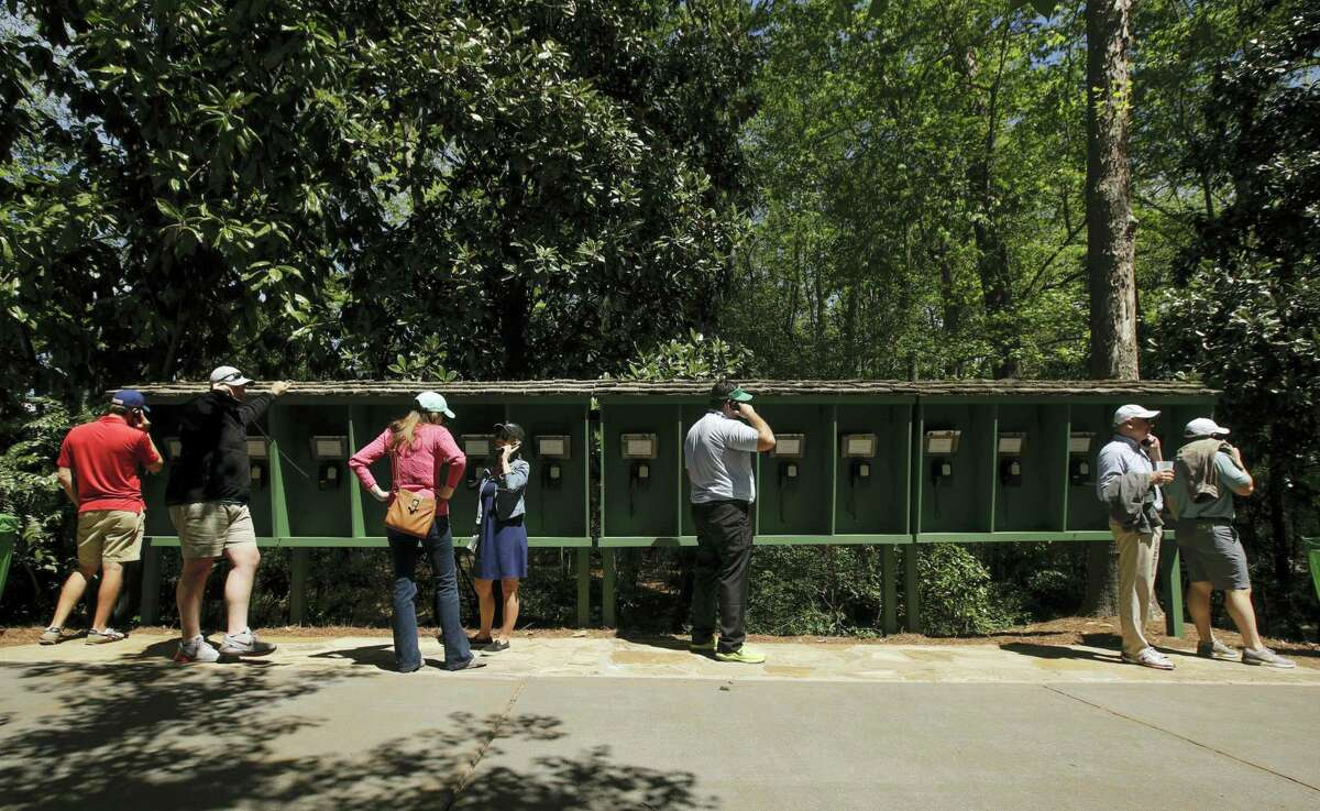 Patrons use pay phones on the Augusta National golf course Saturday in Augusta, Ga. No cell phones are allowed on the course.
