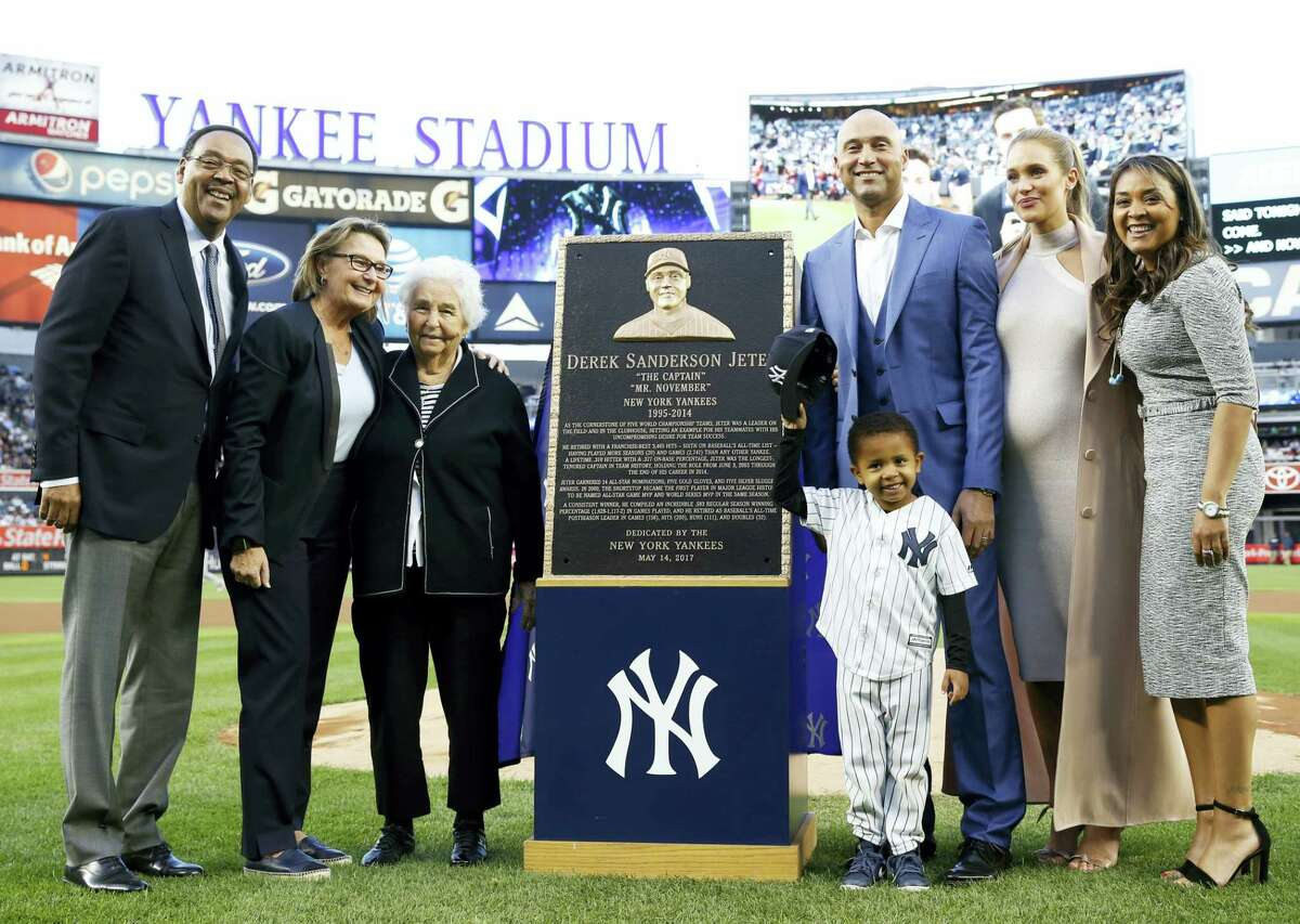 Retired Yankees shortstop Derek Jeter, third from right, poses with members of his family during a pregame ceremony retiring his No. 2 in Monument Park at Yankee Stadium on Sunday.