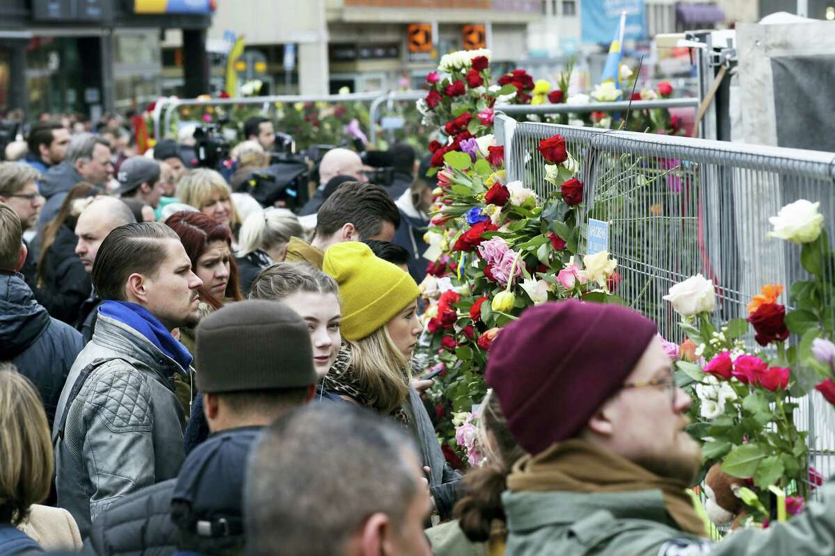 """People lay down flowers at a fence near the department store Ahlens following a suspected terror attack in central Stockholm, Sweden, Saturday, April 8, 2017. Swedish prosecutor Hans Ihrman said a person has been formally identified as a suspect """"of terrorist offences by murder"""" after a hijacked truck was driven into a crowd of pedestrians and crashed into a department store on Friday."""