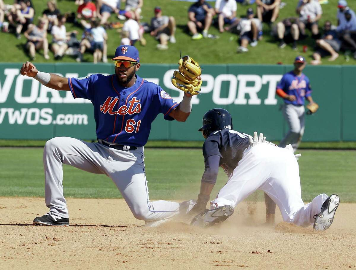 New York Mets shortstop Amed Rosario (61) looks to the umpire for a ruling after Atlanta Braves' Travis Demeritte, right, stole second base in the fifth inning of a spring training baseball game, Friday in Kissimmee, Fla.