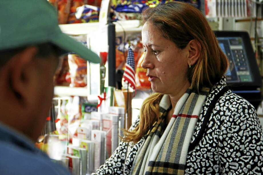 Marcia Chacon assists a patron inside her shop, My Country Store, Jan. 28, 2015, in East Haven. Photo: Esteban L. Hernandez — New Haven Register FILE PHOTO