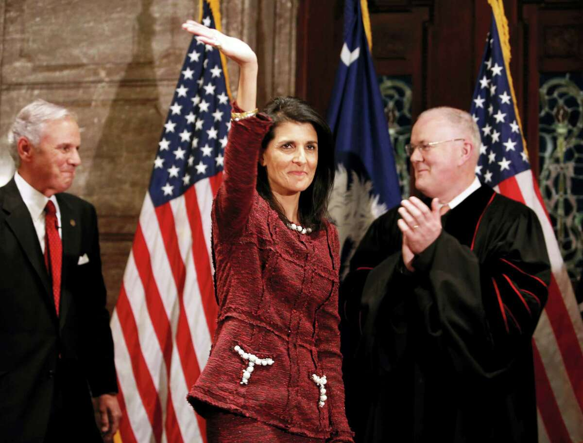 Former South Carolina Governor and current ambassador to the United Nations, Nikki Haley, in middle, waves to the crowd after current Governor Henry McMaster, at left, was sworn in by S.C. Chief Justice Don Beatty during a ceremonial swearing in at the Statehouse Tuesday in Columbia, S.C. Haley resigned as governor after she became ambassador to the United Nations.