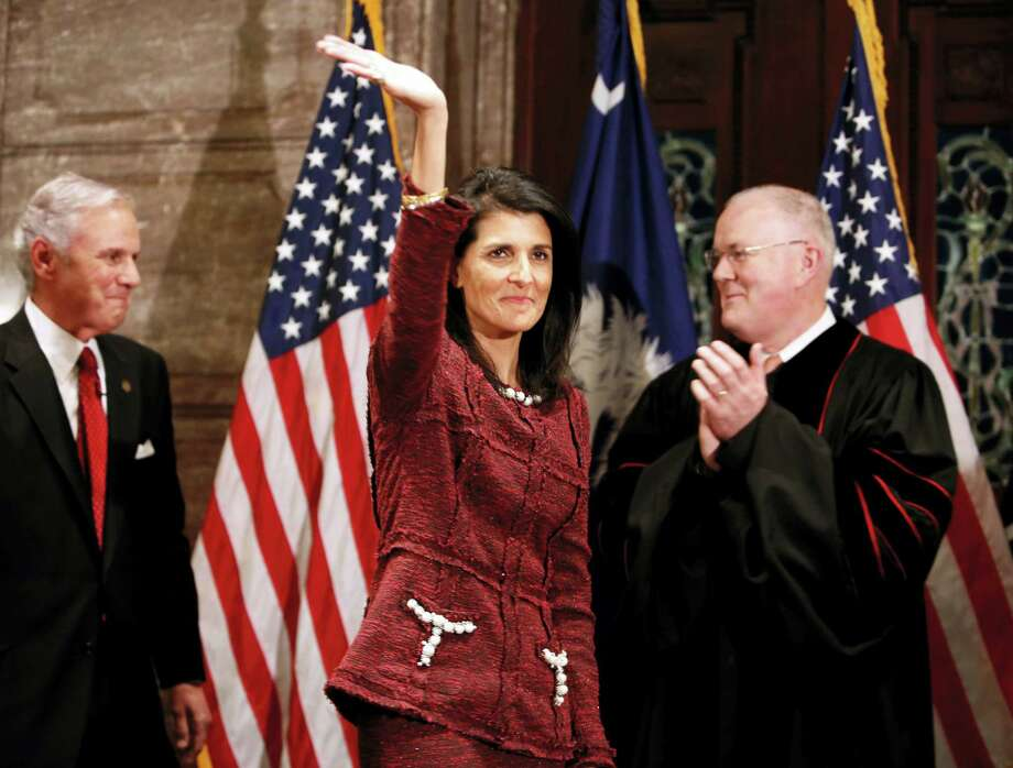 Former South Carolina Governor and current ambassador to the United Nations, Nikki Haley, in middle, waves to the crowd after current Governor Henry McMaster, at left, was sworn in by S.C. Chief Justice Don Beatty during a ceremonial swearing in at the Statehouse Tuesday in Columbia, S.C. Haley resigned as governor after she became ambassador to the United Nations. Photo: Mic Smith — The Associated Press   / Mic Smith Photography LLC