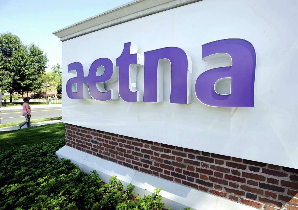 A pedestrian walks past a sign for Aetna Inc., at the company headquarters in Hartford. Aetna and Humana are calling off a $34 billion deal to combine the two major health insurers after a federal judge, citing antitrust concerns, shot down the deal.