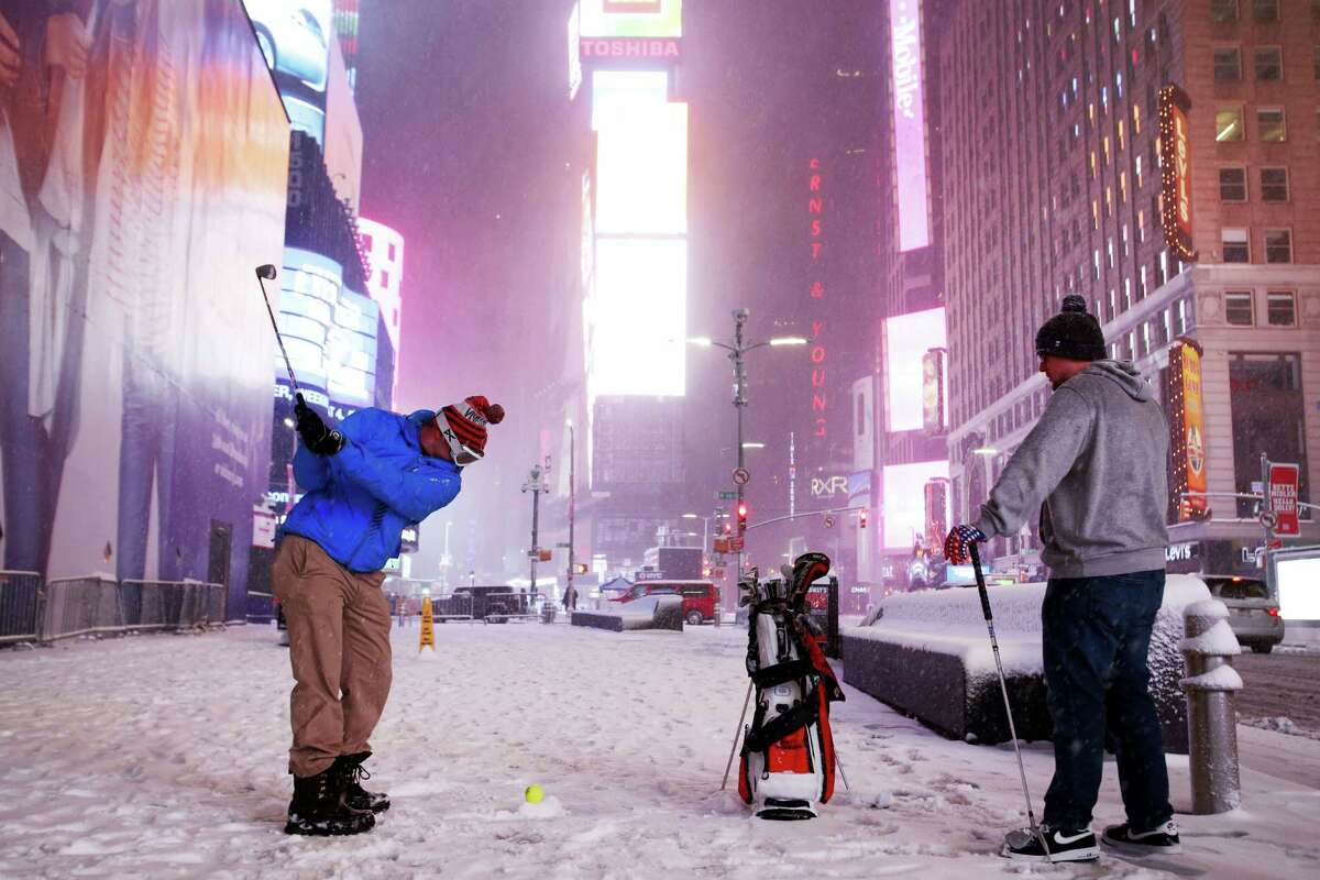 Two men play golf with a tennis ball as a snowstorm sweeps through Times Square on March 14, 2017 in New York. A powerful nor'easter hit the Northeast on Tuesday after a largely uneventful winter, grounding thousands of flights and leading to school and work closures along the coast.