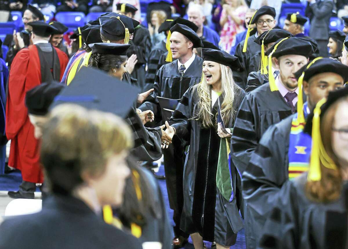 Nicolle Burgwardt, center, and other graduates shake hands with faculty at the TD Bank Sports Center in Hamden Sunday.