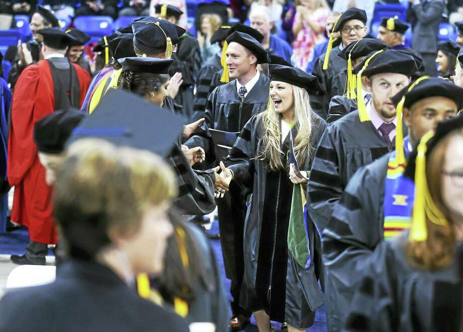 Nicolle Burgwardt, center, and other graduates shake hands with faculty at the TD Bank Sports Center in Hamden Sunday. Photo: Arnold Gold — New Haven Register