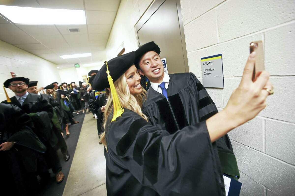 Samantha Lomando (center) and Kevin Kuo (right) take a selfie while waiting for the Frank H. Netter MD School of Medicine Commencement Exercises to begin.