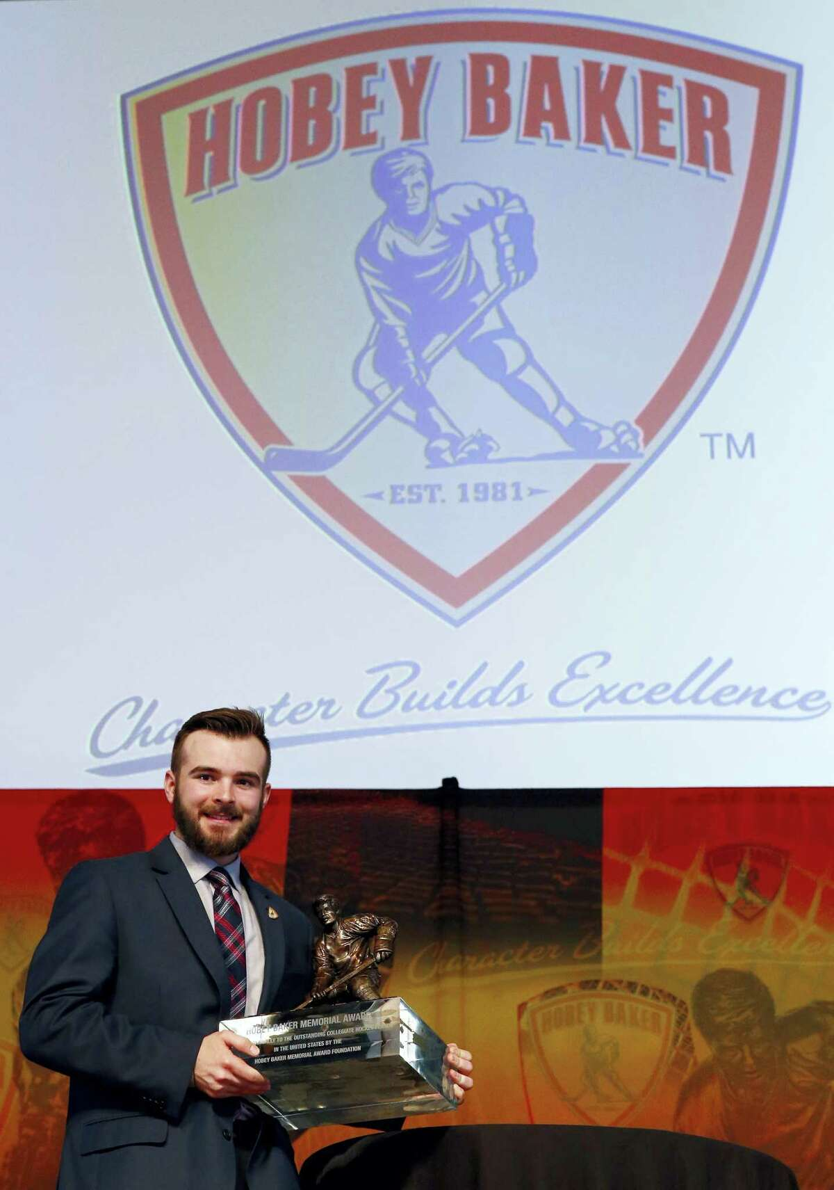 Denver defenseman Will Butcher smiles as he holds his trophy after winning the Hobey Baker Award on Friday.