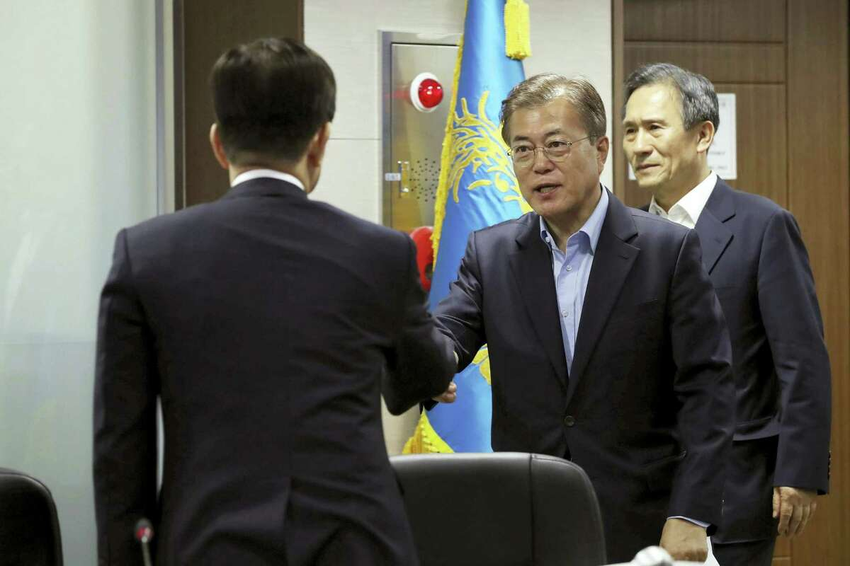 South Korean President Moon Jae-in, center, shakes hands with Defense Minister Han Min-koo upon his arrival to preside over a meeting of the National Security Council at the presidential Blue House in Seoul, South Korea, May 14, 2017. North Korea on Sunday test-launched a ballistic missile that landed in the Sea of Japan, the South Korean, Japanese and U.S. militaries said. The launch is a direct challenge to the new South Korean president elected four days ago and comes as U.S., Japanese and European navies gather for joint war games in the Pacific. (Yonhap via AP)