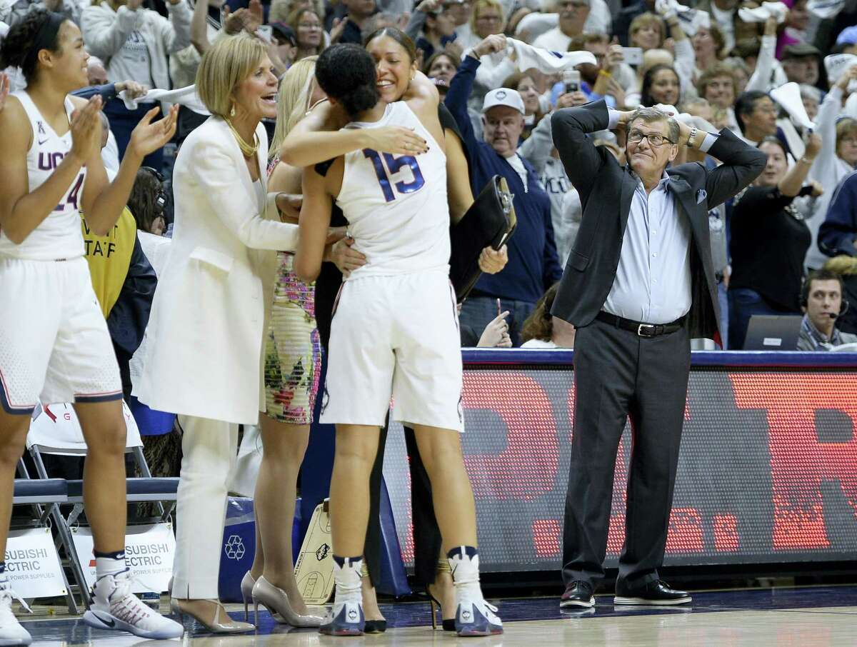 UConn coach Geno Auriemma, right, reacts as Gabby Williams (15) is congratulated by associate head coach Chris Dailey and embraced by assistant coach Marisa Moseley after Monday's win over South Carolina in Storrs. It was the Huskies' 100th straight victory.