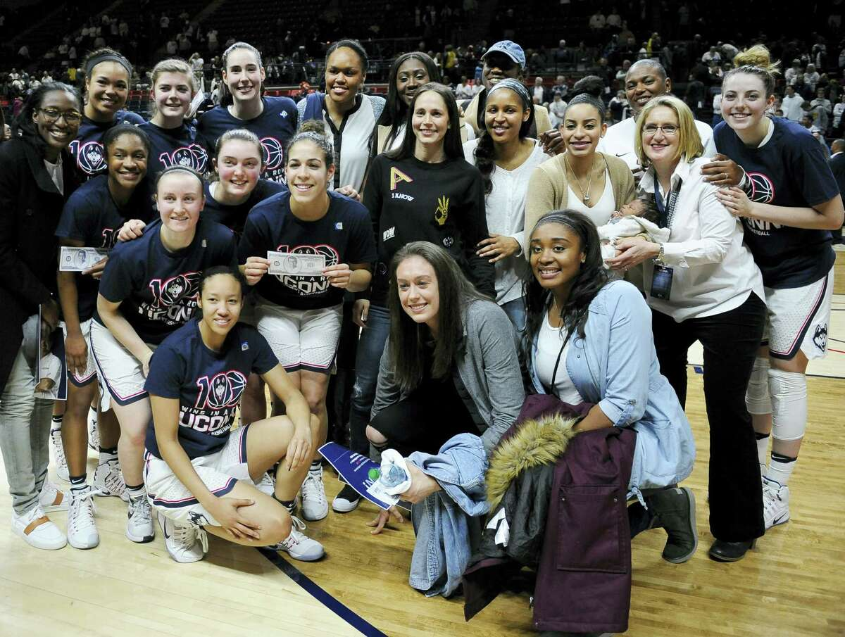 Former and current UConn basketball players gather for a team photograph after Monday's win.
