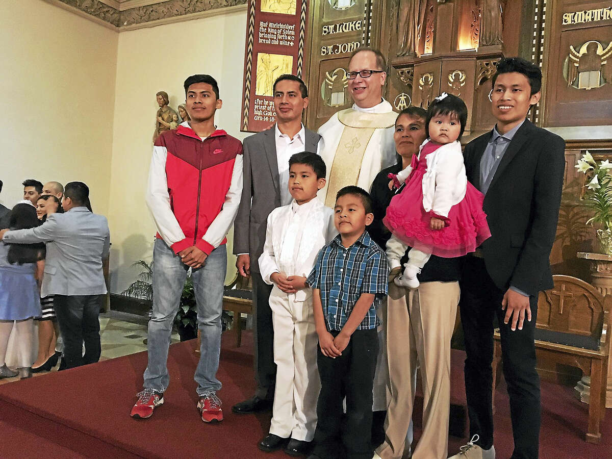 Mary O'Leary — New Haven Register The Rev. James Manship poses with a family whose child received First Communion Sunday. Manship is being transferred to another parish.