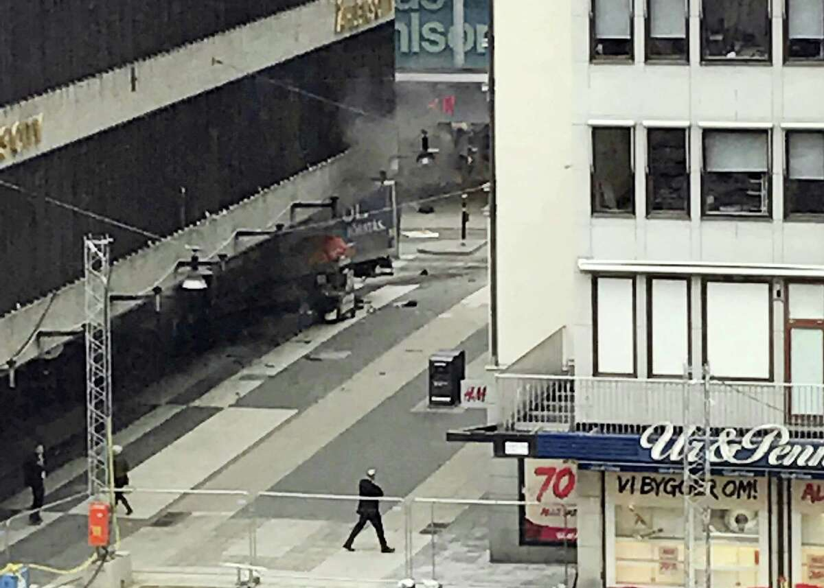 People look on at the scene after a truck crashed into a department store injuring several people in central Stockholm, Sweden, Friday.
