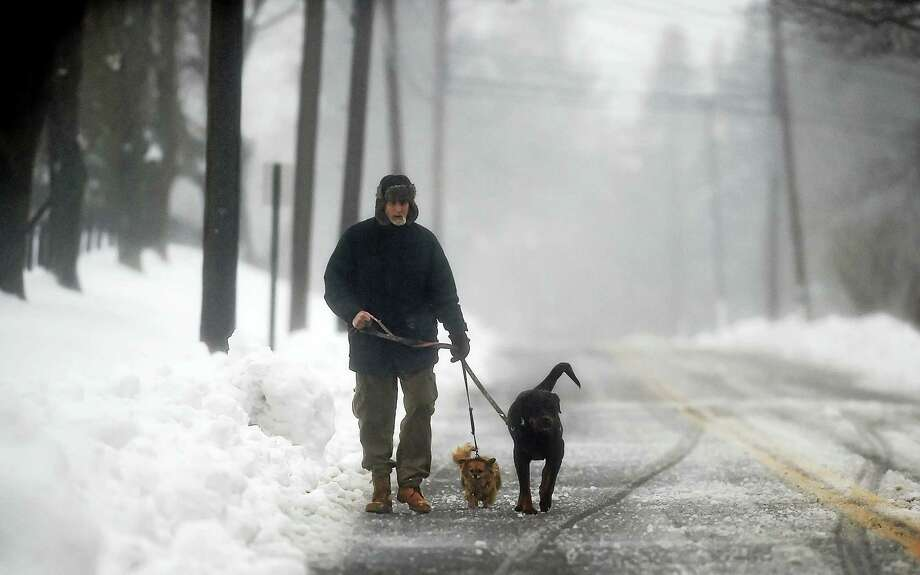 A Ridge Road resident takes his two dogs for a walk walk in Middletown during the blizzard,Tuesday, March 14, 2017. (Catherine Avalone/New Haven Register) Photo: Catherine Avalone/New Haven... / Catherine Avalone/New Haven Register