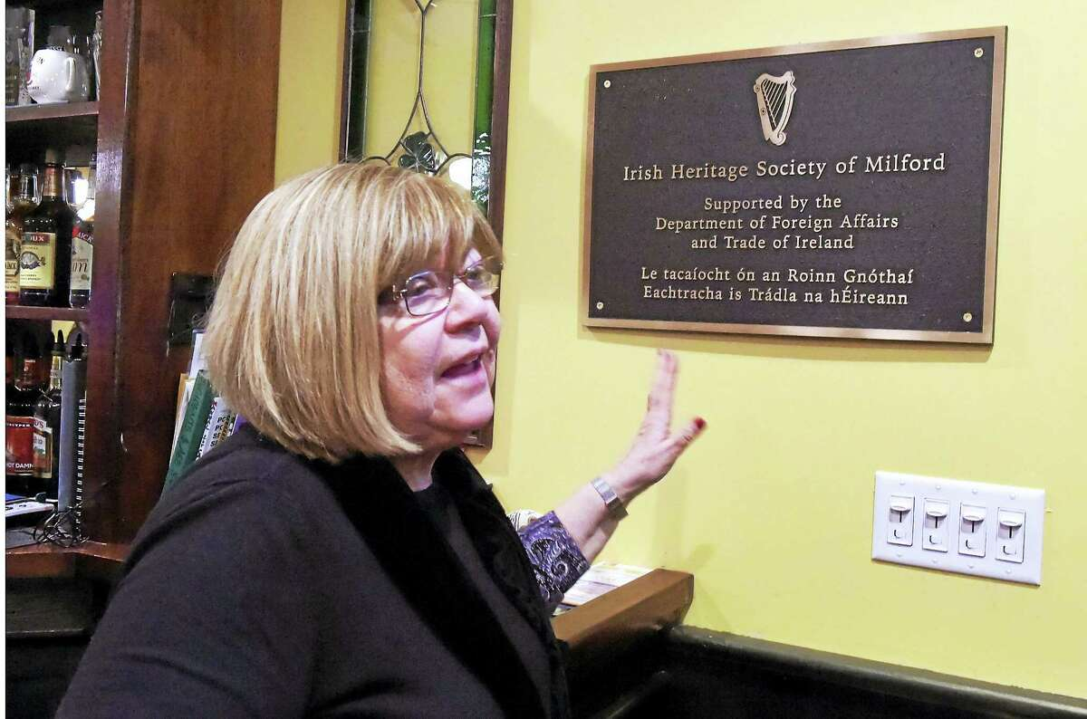 Kathleen Dunn Stern, president of the Irish Heritage Society of Milford shows off a plaque given to the society by the government of Ireland.