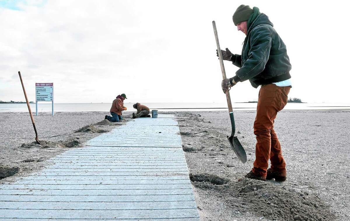 Ryan Maher (right), a seasonal maintenance worker with the Parks Division of the Connecticut DEEP, and coworkers remove a handicapped ramp on the beach at Silver Sands State Park in Milford in 2014.