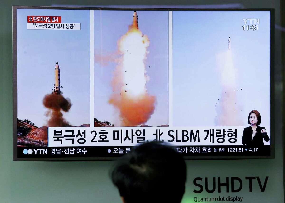 """A man watches a TV news program showing photos published in North Korea's Rodong Sinmun newspaper of North Korea's """"Pukguksong-2"""" missile launch at Seoul Railway station in Seoul, South Korea on Feb. 13, 2017. In an implicit challenge to President Donald Trump, North Korea fired a ballistic missile early Sunday in its first such test of the year. The letters read """"Pukguksong-2 missile and advanced Submarine-Launched Ballistic Missiles."""""""