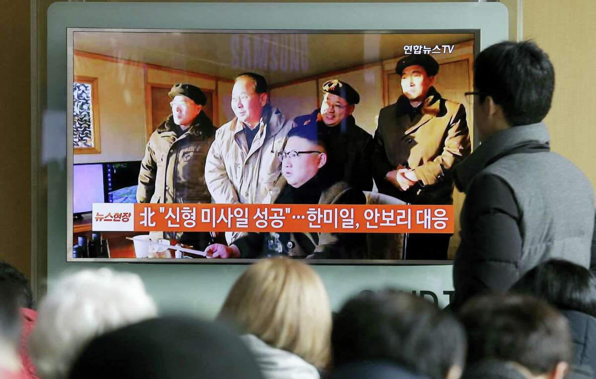 """People watch a TV news program showing a photo published in North Korea's Rodong Sinmun newspaper of North Korean leader Kim Jong Un, at Seoul Railway station in Seoul, South Korea, Monday, Feb. 13, 2017. In an implicit challenge to President Donald Trump, North Korea fired a ballistic missile early Sunday in its first such test of the year. The sign read """"Successful missile launch."""""""