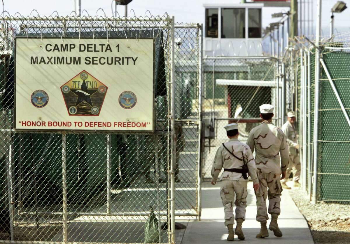 """U.S. military guards walk within Camp Delta military-run prison, at the Guantanamo Bay US Naval Base, Cuba. A draft executive order shows President Donald Trump asking for a review of America's methods for interrogation terror suspects and whether the U.S. should reopen CIA-run """"black site"""" prisons outside the U.S."""