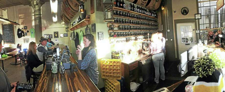 The bar/serving area of Firefly Hollow Brewing Co., with growlers sitting above servers in the late-afternoon sun. Photo: Joe Amarante — New Haven Register