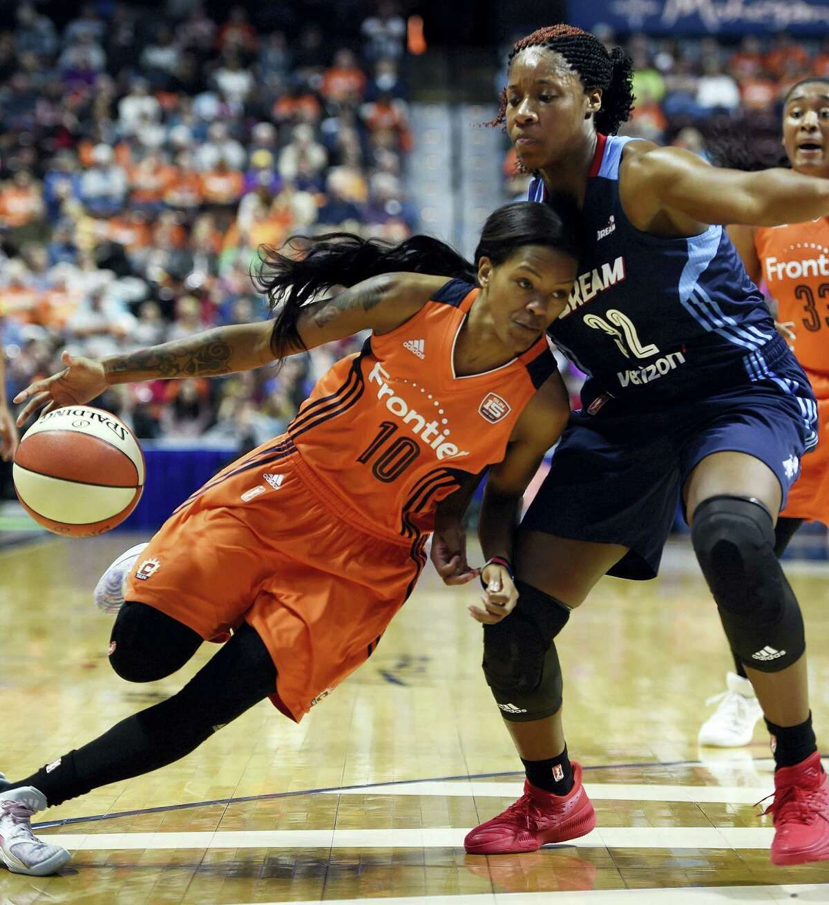 Former Hillhouse standout Bria Holmes, right, defends the Sun's Courtney Williams in the first half Saturday in Uncasville.