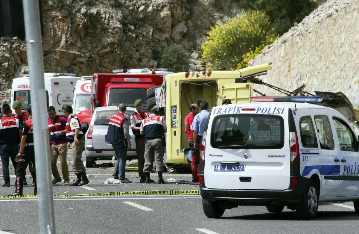 Turkish police officers work next to an overturned bus at the scene of a traffic accident, near Marmaris, western Turkey, Saturday, May 13, 2017. Turkish authorities say that over 20 people have died and nearly a dozen injured are in critical condition after a tour bus tipped over, fell 15 meters (50 feet) down a cliff and then hit a car on a serpentine mountain road.