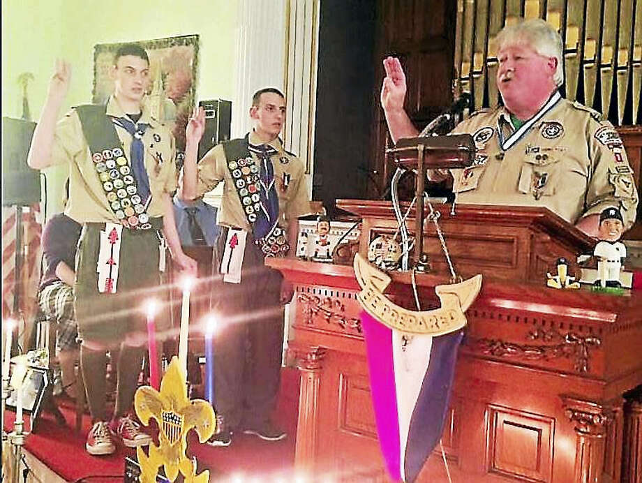 Eagle Scouts Matthew Kish, left, and Ryan Kish, right, get oath from fellow Eagle Scout Charles Stankye III. Photo: Contributed Photo