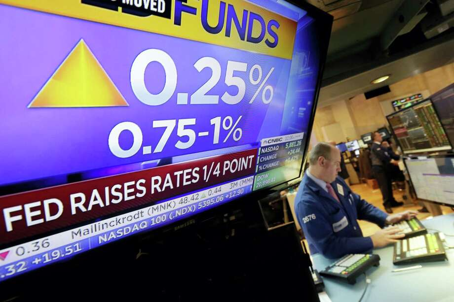 Specialist Edward Loggie works at his post as a television screen on the floor of the New York Stock Exchange shows the decision of the Federal Reserve on March 15, 2017. The Fed's key short-term rate is rising by a quarter-point to a still-low range of 0.75 percent to 1 percent. Photo: AP Photo — Richard Drew   / AP