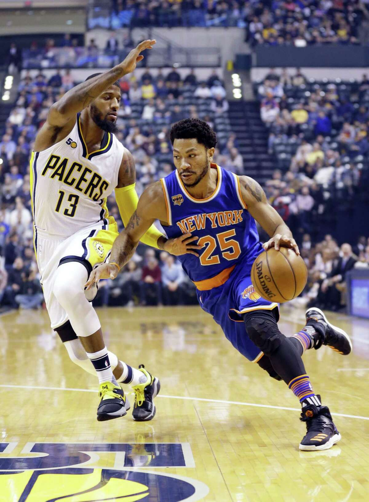 New York Knicks guard Derrick Rose (25) drives on Indiana Pacers forward Paul George (13) during the first half of an NBA basketball game in Indianapolis on Jan. 23, 2017.
