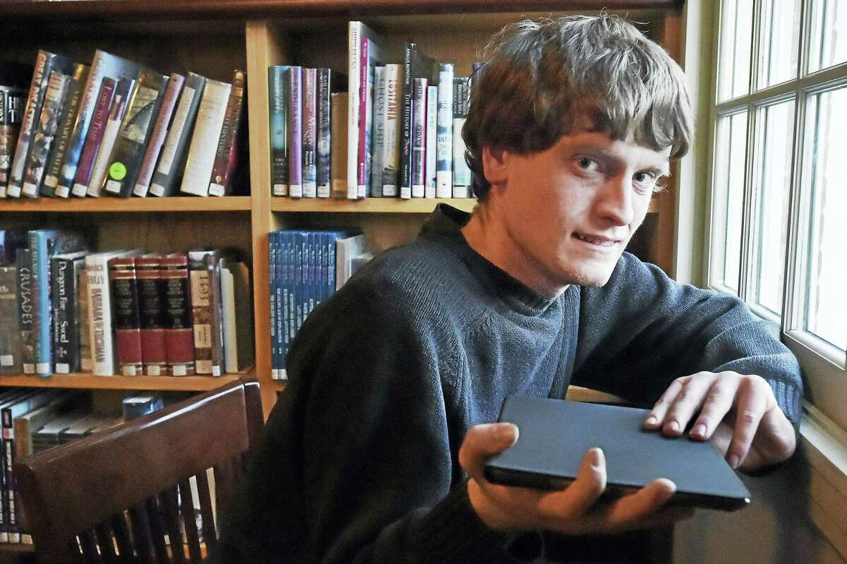 Tommy Canning of Madison holds his iPad Wednesday at Atwater Memorial Library in North Branford.