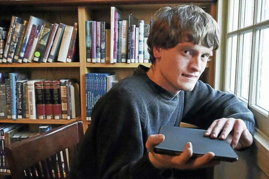 Tommy Canning of Madison holds his iPad  Wednesday at Atwater Memorial Library in North Branford. Photo: Catherine Avalone — New Haven Register   / Catherine Avalone/New Haven Register
