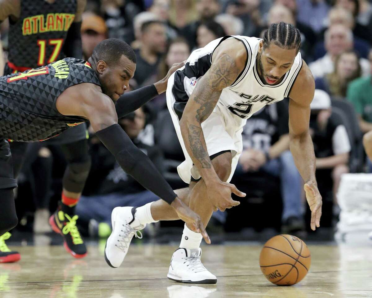 Atlanta Hawks forward Paul Millsap (4) knocks the ball away from San Antonio Spurs forward Kawhi Leonard (2) during the second half of an NBA basketball game on Monday, March 13, 2017 in San Antonio. Spurs won 107-99.