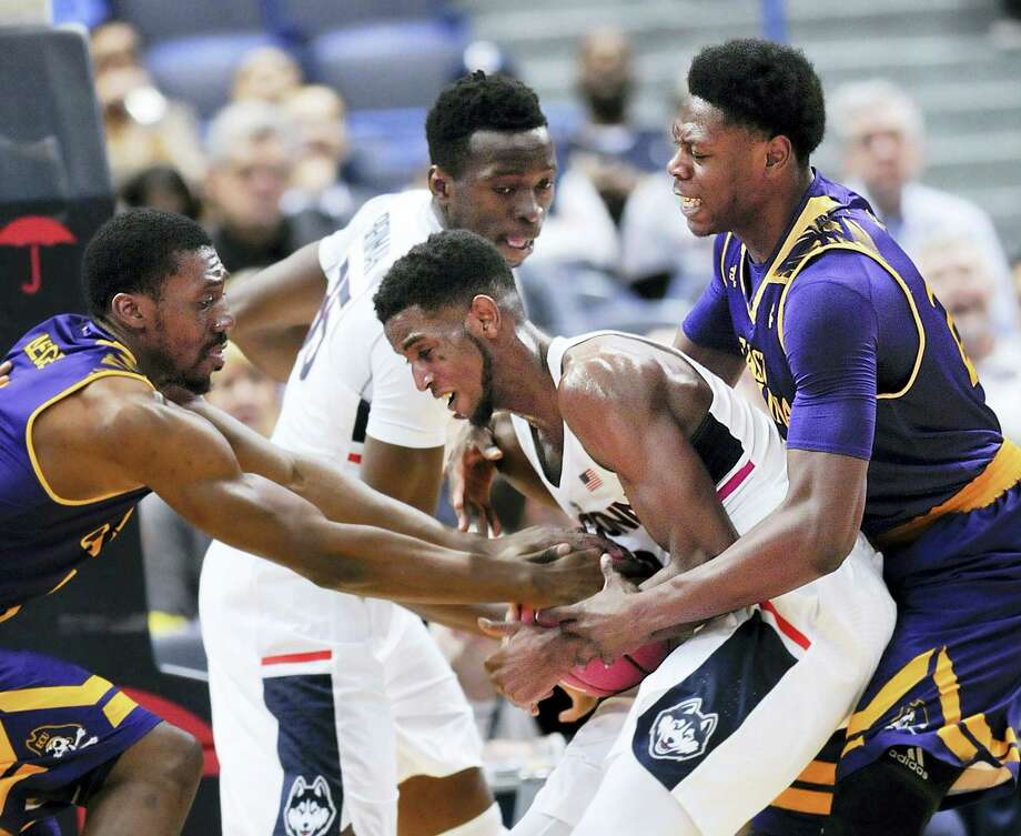 UConn's Kentan Facey (12) hangs on to a rebound against East Carolina defenders in the second half of Sunday's 72-65 win for the Huskies over East Carolina. Photo: STEPHEN DUNN — The Associated Press   / FR171426 AP