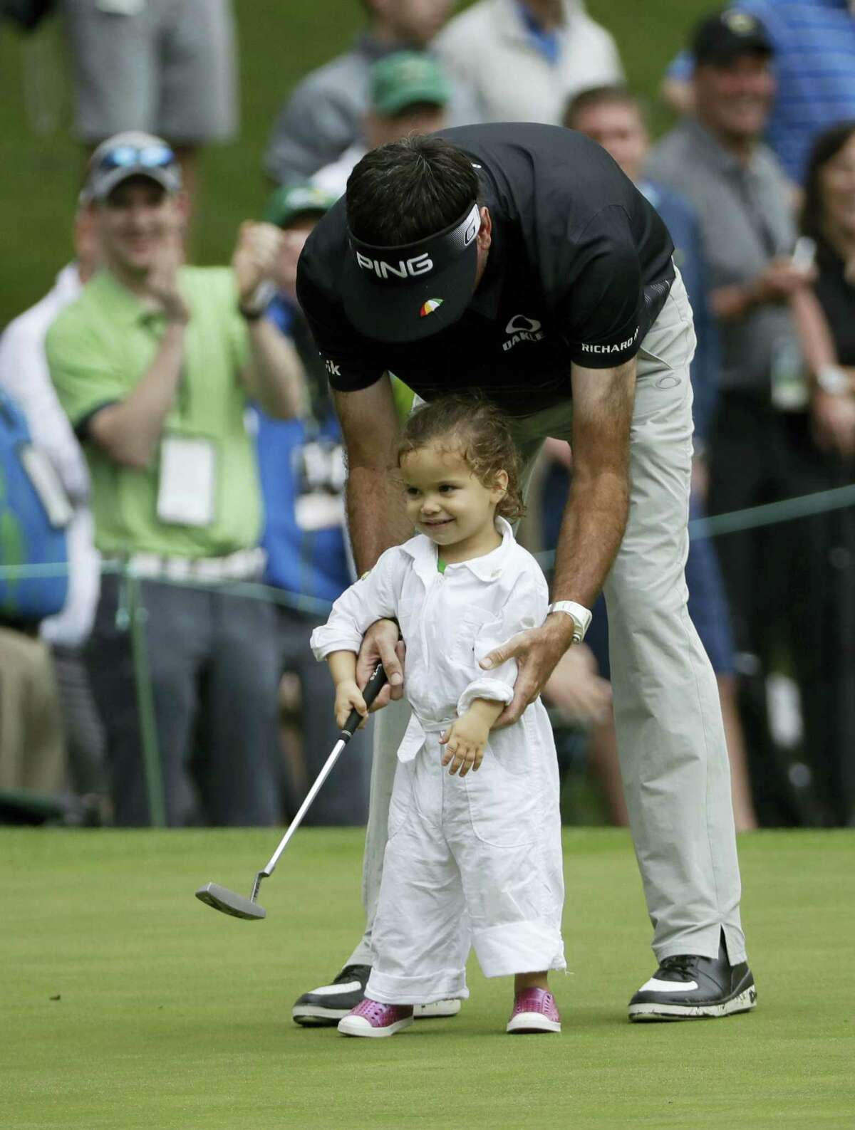 Bubba Watson helps his daughter Dakota putt during the par three competition at the Masters golf tournament Wednesday in Augusta, Ga.