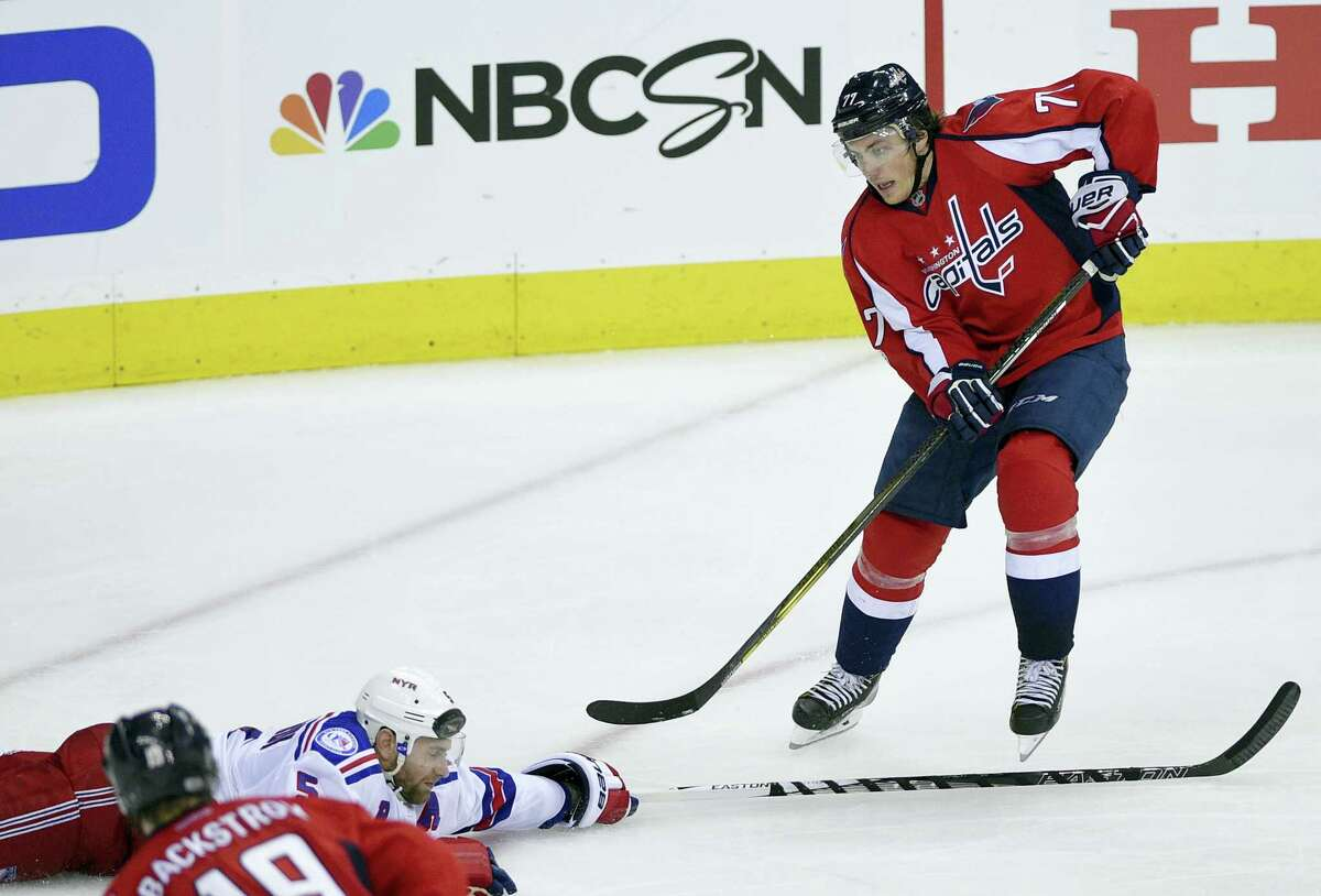 Washington Capitals right wing T.J. Oshie (77) passes the puck past New York Rangers defenseman Dan Girardi (5) during the third period of an NHL hockey game, Wednesday, April 5, 2017, in Washington. The Capitals won 2-0. (AP Photo/Nick Wass)