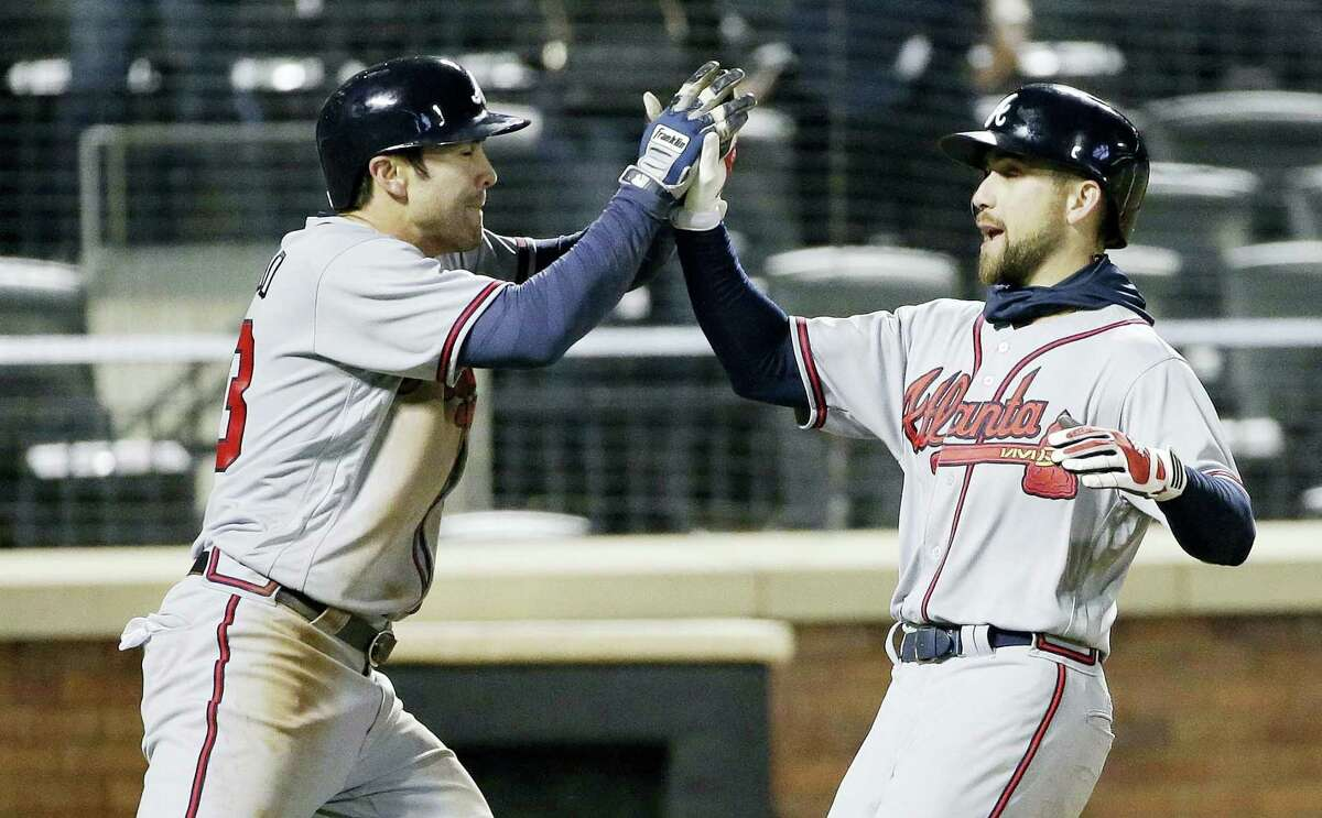 Atlanta Braves' Chase d'Arnaud, left, and Ender Inciarte, right, celebrate after they score on a two-run double by Matt Kemp during the twelfth inning of a baseball game, Wednesday in New York.