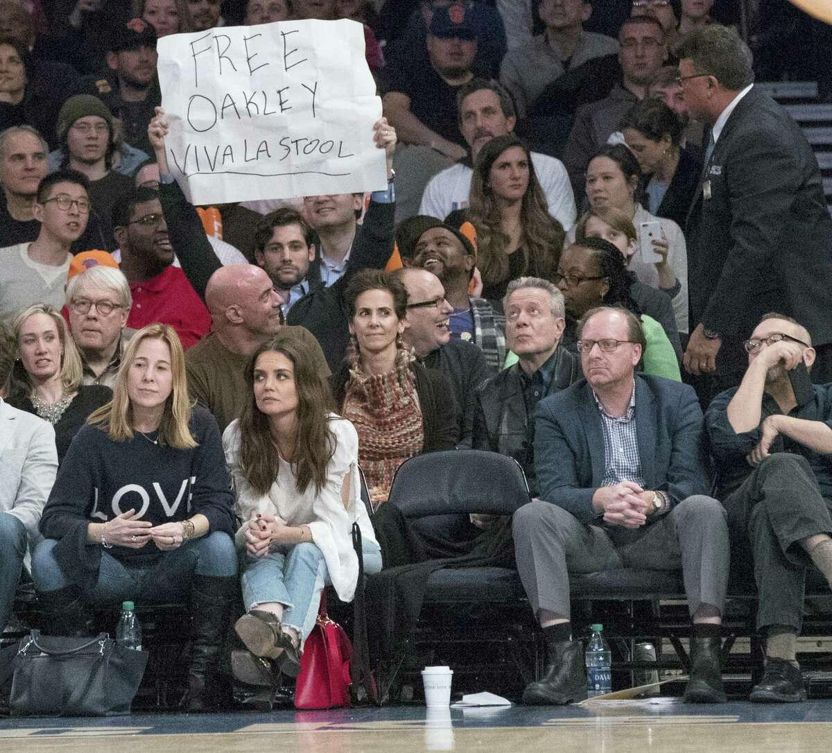 "A fan holds a ""Free Oakley"" sign behind Madison Square Garden chairman James Dolan's empty seat during the second half of an NBA basketball game between the New York Knicks and the Denver Nuggets on Feb. 10, 2017 at Madison Square Garden in New York.The Nuggets won 131-123."