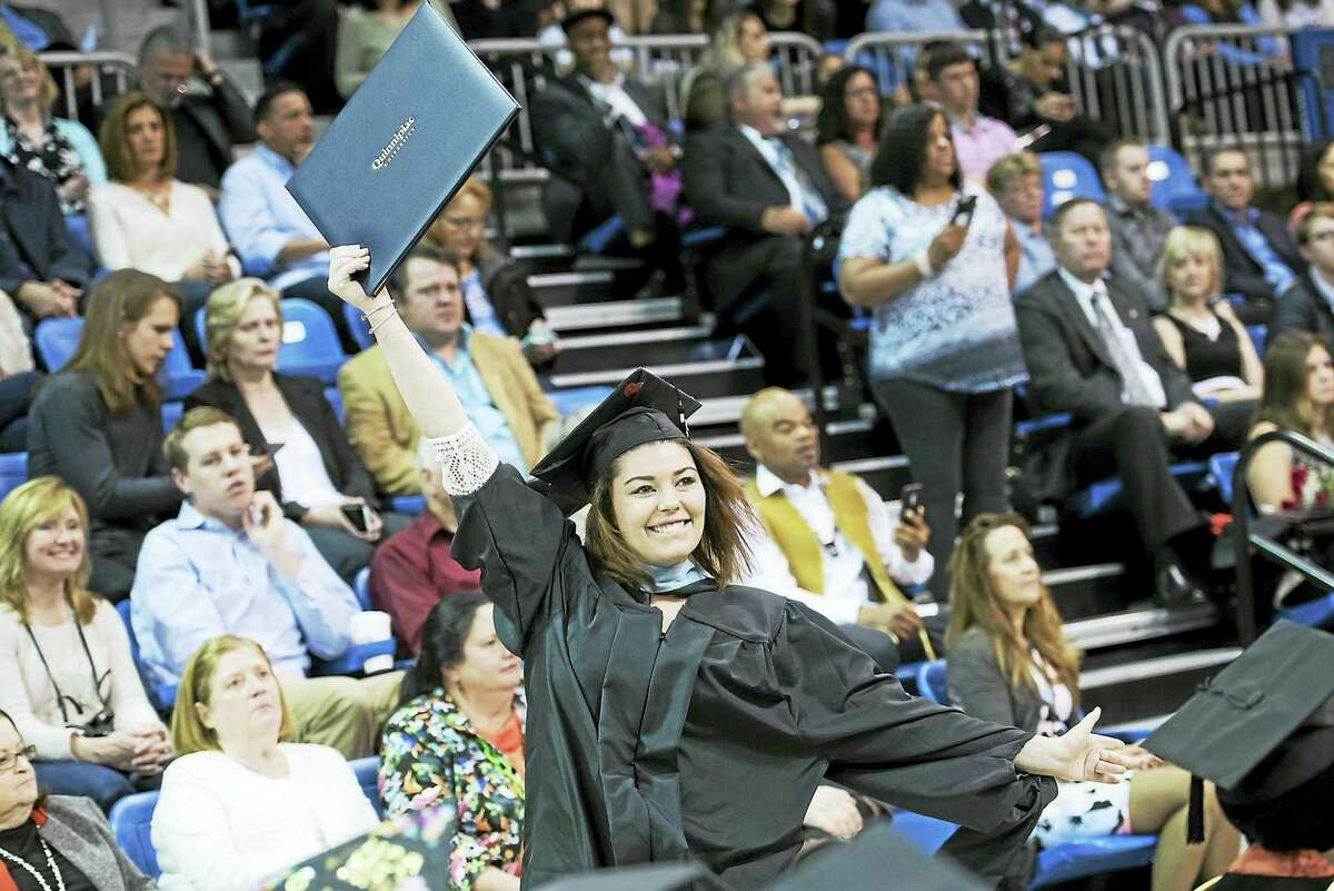 Quinnipiac University graduate McKenzie Abraham waves her diploma after receiving her master of arts in teaching elementary education degree during commencement exercises on Saturday, May 13, at the TD Bank Sports Center.