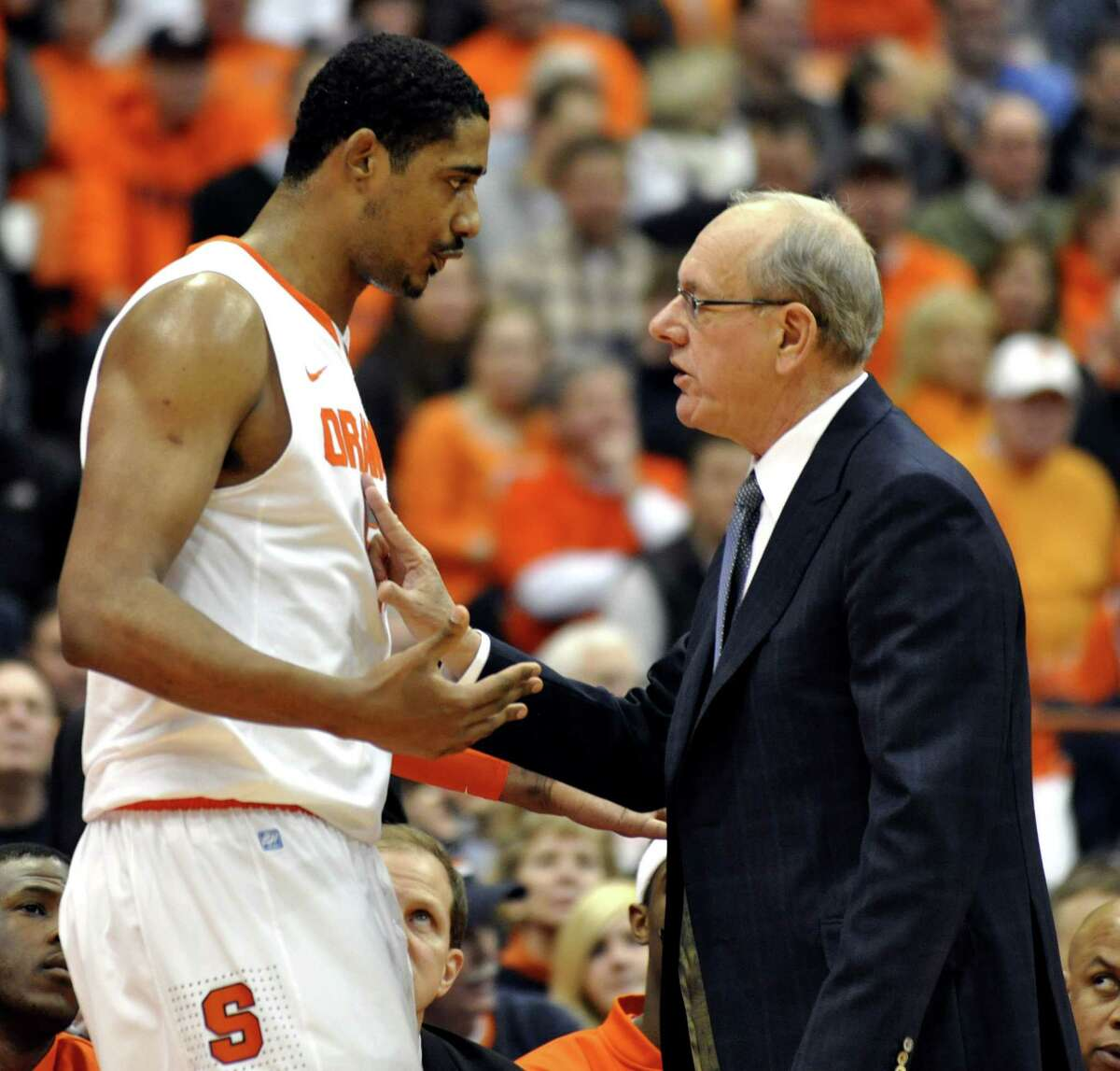 In this Jan. 15, 2011 photo, Syracuse head coach Jim Boeheim, right, talks with Fab Melo during the first half against Cincinnati in an NCAA college basketball game in Syracuse, N.Y.