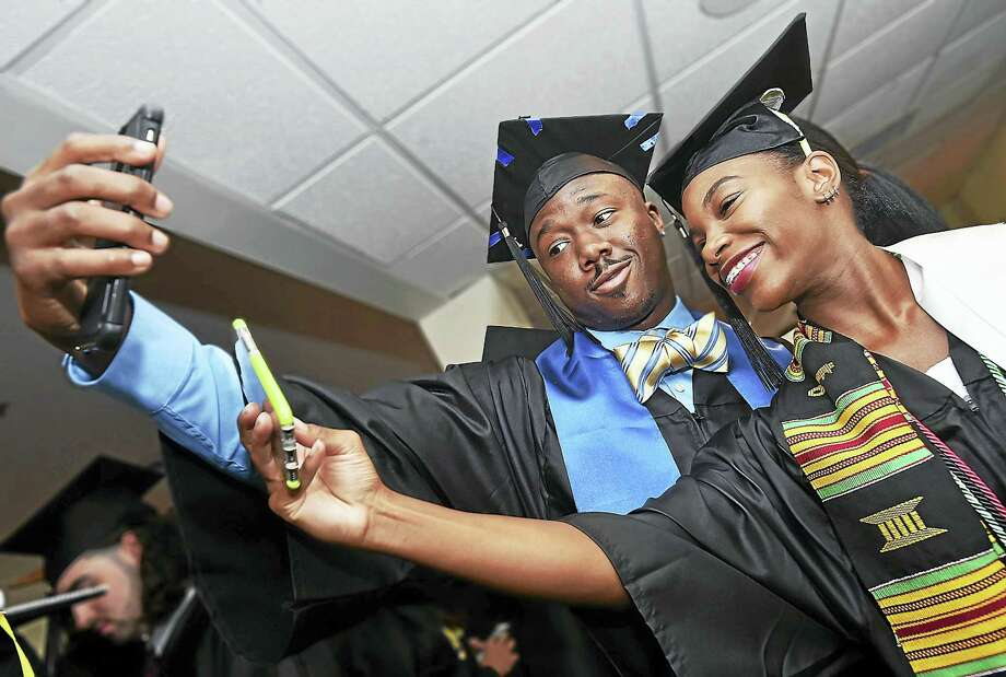 Rishawn Harris, of Springfield, Massachusetts and Taylor Stewart-Grant, of Bronx, New York take a dual selfie at the University of New Haven commencement exercises for the College of Business and the Henry C. Lee College of Criminal Justice and Forensic Sciences, Saturday at the Toyota Presents Oakdale Theatre at 95 South Turnpike Road in Wallingford. Harris received a Bachelor of Science in sports management and Stewart-Grant received a Bachelor of Science in accounting. Photo: Catherine Avalone — New Haven Register   / Catherine Avalone/New Haven Register