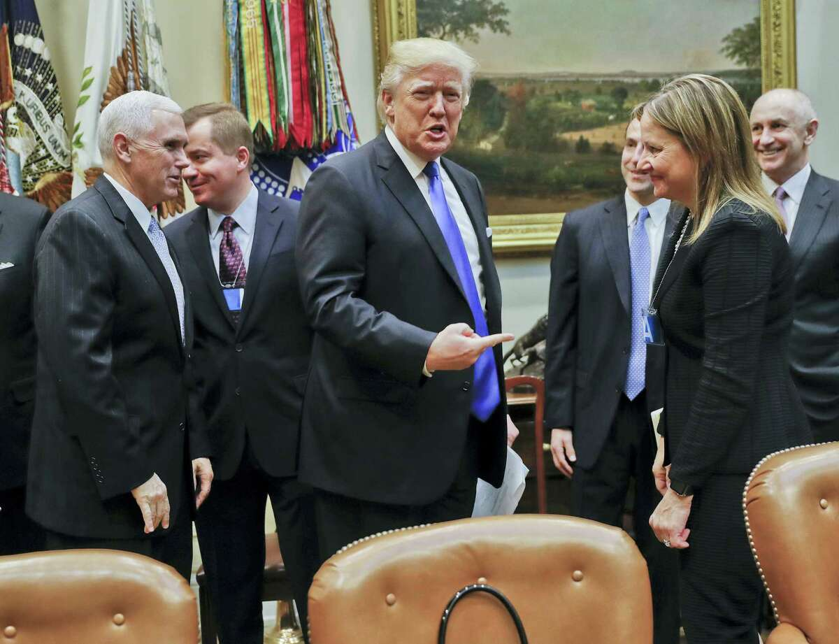 President Donald Trump gestures toward GM CEO Mary Barra, right, before the start of a meeting with automobile leaders in the Roosevelt Room of the White House in Washington Tuesday. From left are Vice President Mike Pence, left, and Matt Blunt, president of the American Automotive Policy Council and the former governor of Missouri.