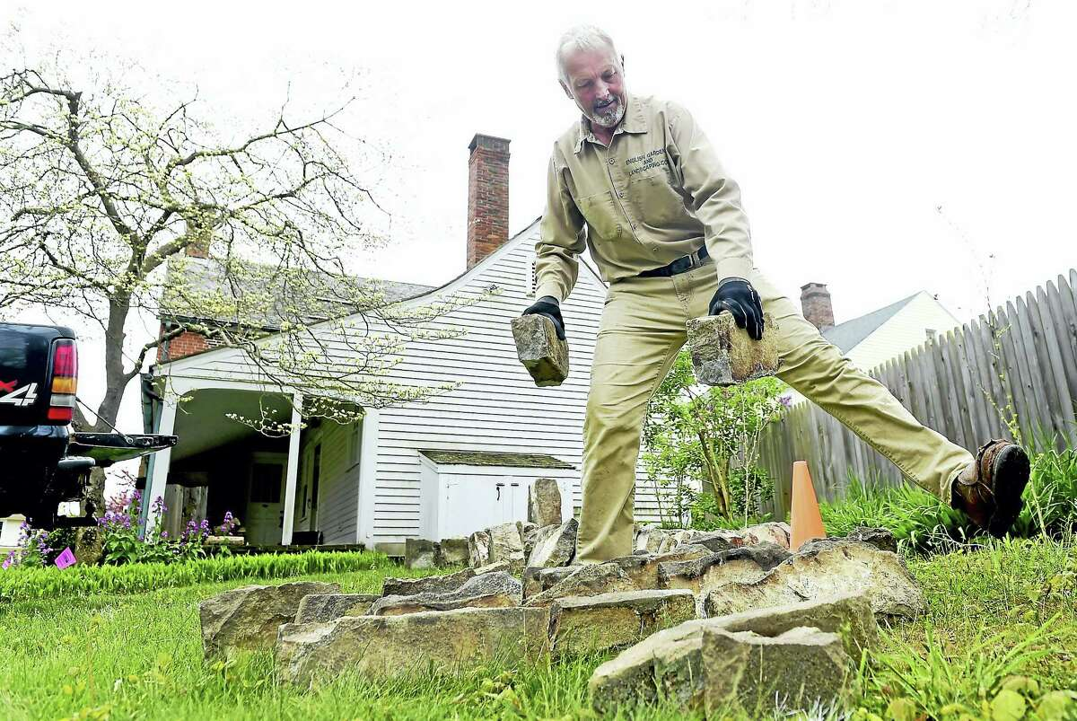 """(Peter Hvizdak - New Haven Register) Master Stone Artisan Andrew Pighills of English Gardens and Landscaping of Killingworth place pieces of a mid-19th century historic smokehouse dismantled from its original location at the St. Alexis Orthodox Church in Clinton to its new location behind the """"Old Brick"""" house of the Clinton Historical Society."""