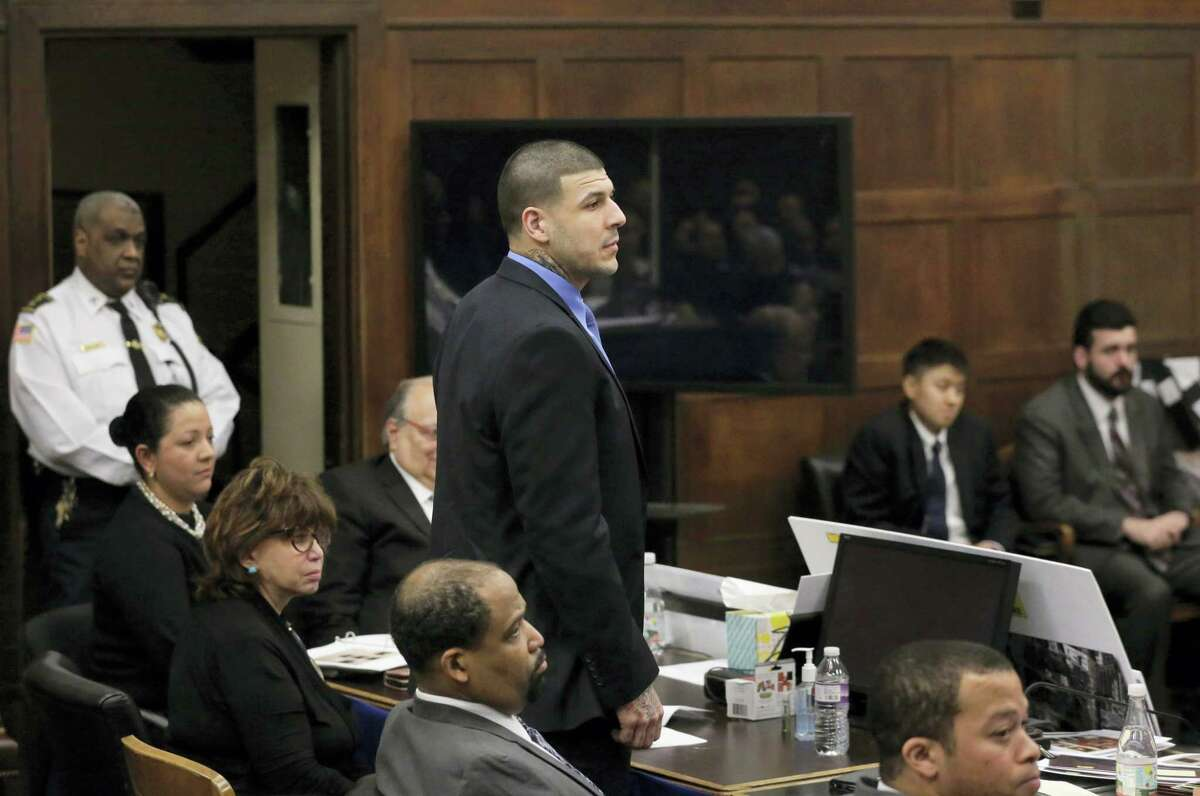 Former New England Patriots tight end Aaron Hernandez, center, stands when asked to do so by defense attorney Jose Baez, not shown, as Baez makes closing arguments Thursday in Boston.