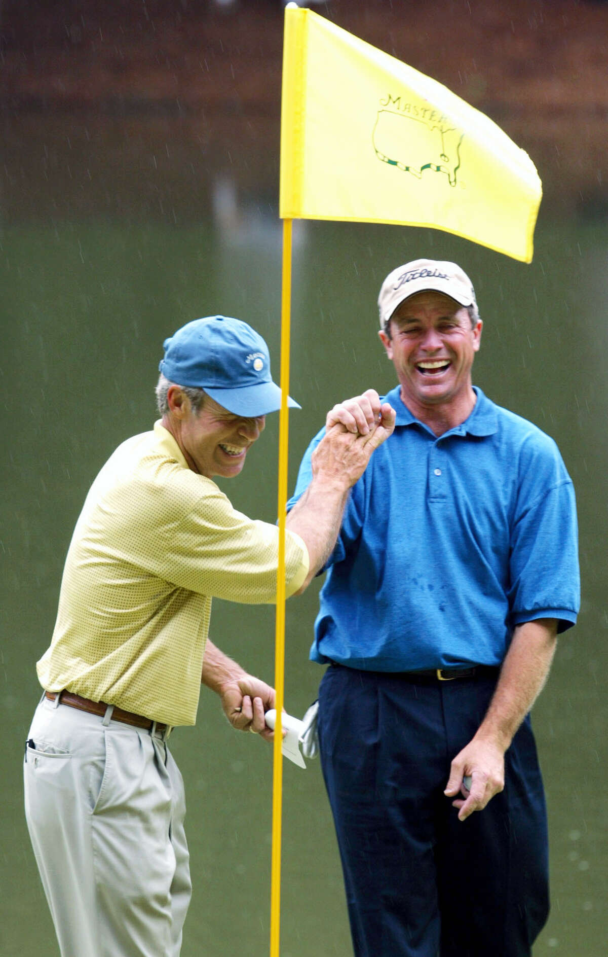 """In this file photo, Jerry Pate, right, is all smiles as he is greeted by Ben Crenshaw, left, at the ninth green after sinking the ball for par on a penalty shot from the tee box in the Masters' Par 3 Contest at the Augusta National Golf Club in Augusta, Ga. Augusta National has sent letters to its honorary invitees to inform them that the Par 3 Contest will be limited to players in the field and past Masters champions. U.S. Open, British Open and PGA Championship winners are exempt to the Masters for five years. After that, they become """"honorary invitees,"""" along with all past U.S. Amateur champions. Pate is a Pate, a former U.S. Amateur and U.S. Open champion."""
