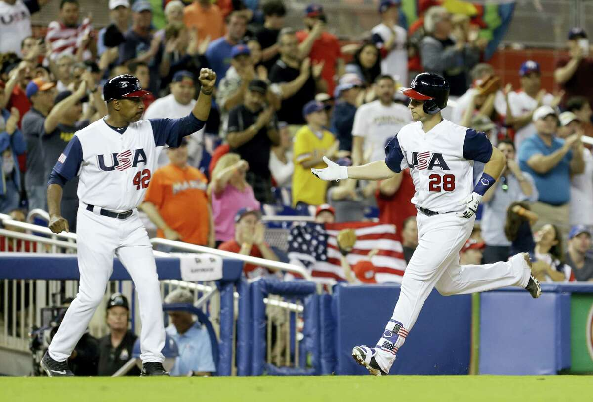 United States' Buster Posey (28) rounds third base after hitting a solo home run as third base coach Willie Randolph prepares to congratulate Posey in the seventh inning in a first-round game of the World Baseball Classic against Canada, Sunday, March 12, 2017, in Miami. The United States won 8-0. (AP Photo/Alan Diaz)