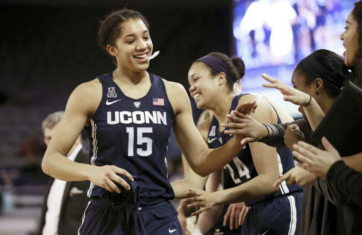 UConn's Gabby Williams (15) is congratulated by teammates after achieving a triple-double, the fifth in school history, during the second half of the Huskies' 91-44 win, the program's record 94th straight victory.