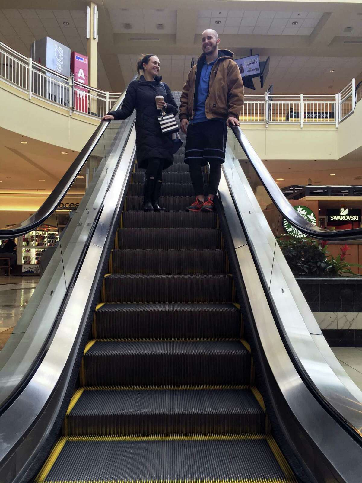 Courtney Taylor and her boyfriend, Zach Tobias, ride the escalator at a mall in Whitehall, Pa., on Feb. 9, 2017. Taylor and Tobias don't mix shopping with politics, but say it seems to be happening more often during the Donald Trump era as activists who either oppose or support the president target stores and brands for boycotts. (AP Photo/Michael Rubinkam)