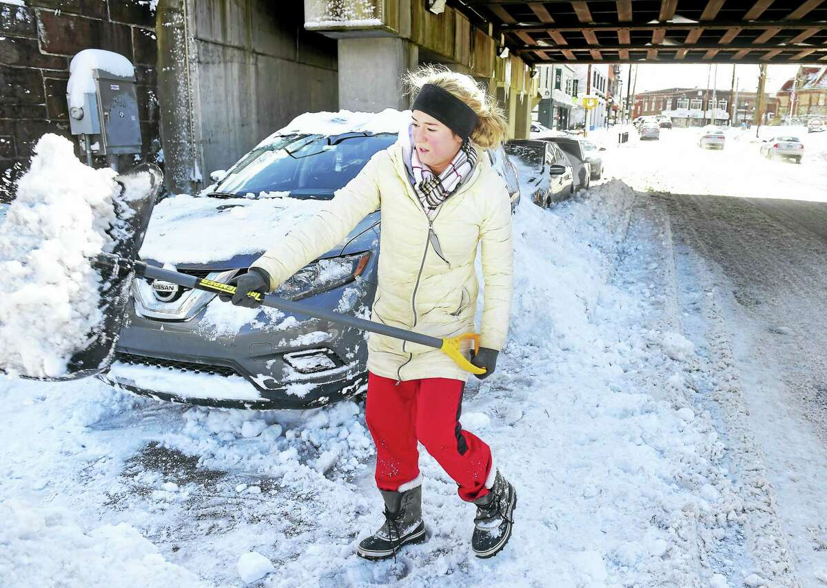 Meghan Weiser of Milford shovels out her car from the previous day's snow on River Street in Milford Friday.